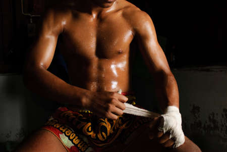 thai boxing: The muscular fighter tying tape around his hand preparing to fight Stock Photo