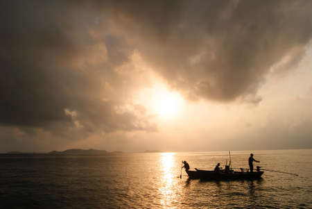 fisherman on boat in the sunrise at Koh Chang   Thailand 写真素材
