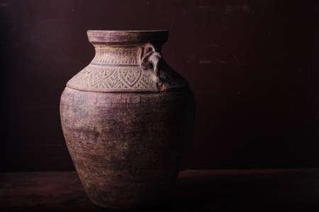 Earthenware jug standing on dark room or tiles  with copyspace photo