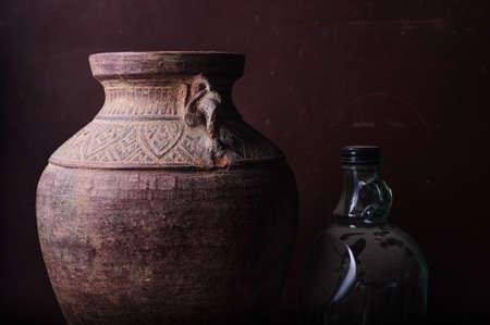 Earthenware jug standing on dark room photo
