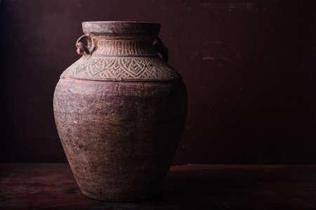 Earthenware jug standing on dark room or tiles  with copyspace