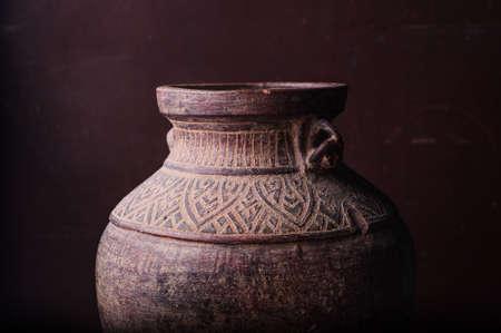 Earthenware jug standing on dark room