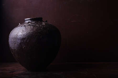 Earthenware jug standing on dark room or tiles  with copyspace