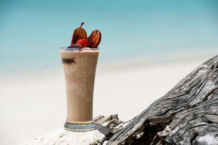 tropical drink at sandy beach on the ocean photo