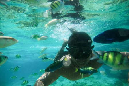 Morgan Homme nage sous la surface avec de nombreux poissons