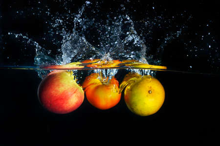 apples falling and splashing into clear water Stock Photo