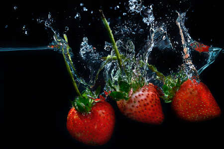 fresh strawberry dropped into water with splash on black backgrounds photo