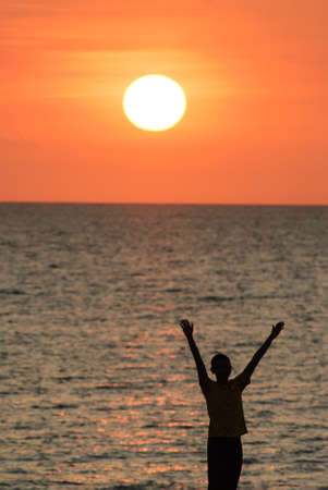 Man with his hands up watching the sun set photo