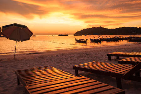 Sunbeds on the beach at sunset, Thailand photo