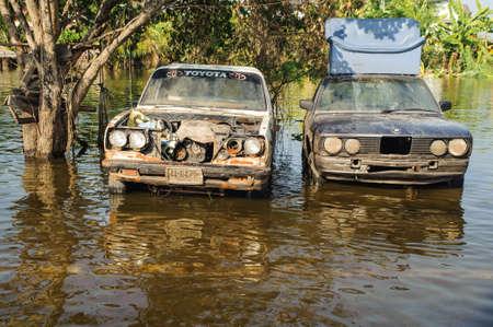 Vieille voiture submergée dans une route inondée.