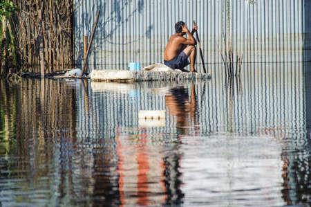 Man asseoir la sécurité sur une section de la route inondée à Bangkok