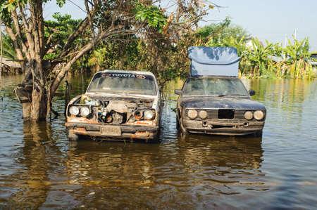 Une vieille voiture se trouve submergé dans une route inondée.