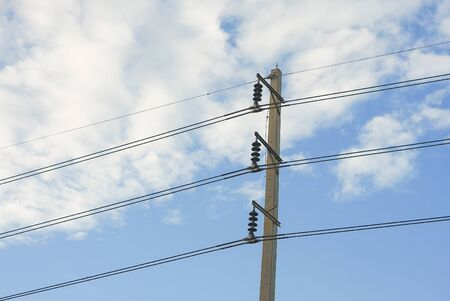 electrical system: Electrical poles of high voltage 115 kV in white and blue sky.