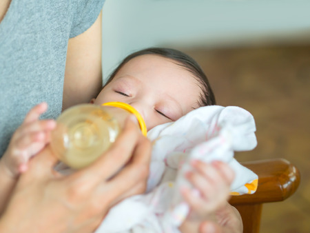 daugther: Mother feeding bottle milk her daugther Stock Photo
