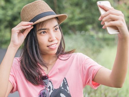 mirthful: Asian girl taking selfie by smartphone.