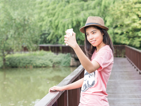 enchant: Asian girl taking selfie by smartphone on wooden pedestrian in the park.