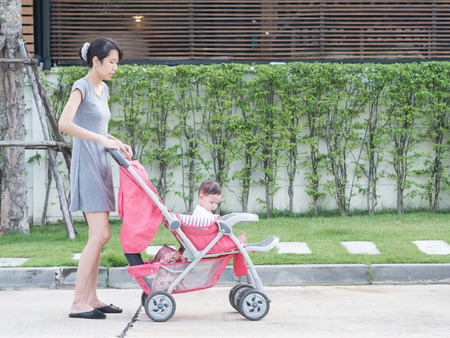 Asian mother and baby in stroller, in village. Stock Photo