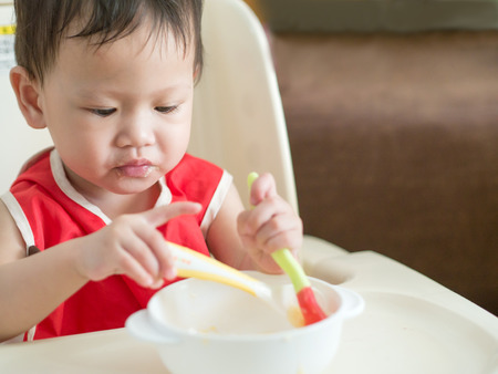 Asian toddler learn to eat meal herself. Stock Photo