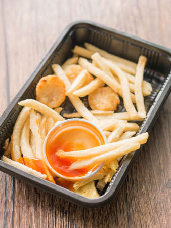 dietetics: French fried and ketchup in black bowl on wooden table.