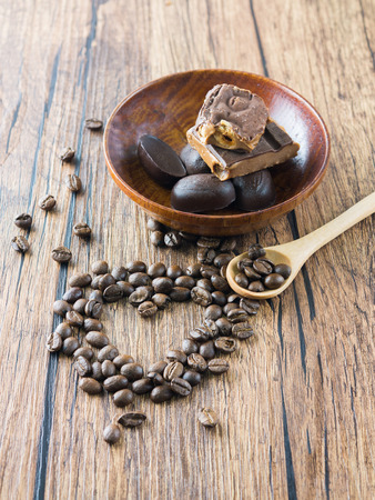 morsel: Coffee beans arranged heart figure with spoon and chocolate bars. Stock Photo