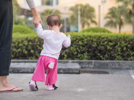 toddler walking: Asian toddler walking first step in park morning. Mother hold baby hand. Stock Photo