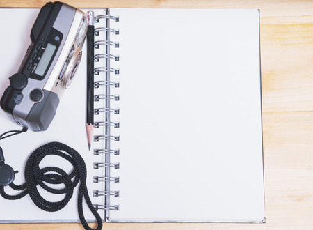 compact camera: Notebook with old film compact camera and black pencil on wooden table.
