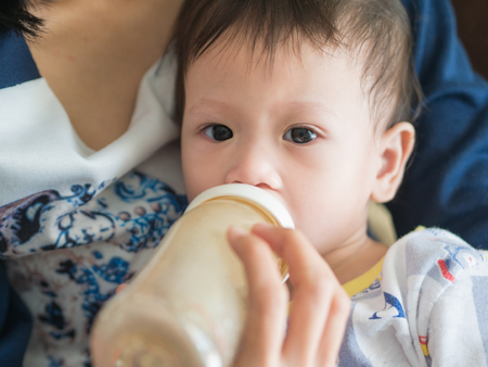 nursling: Asian mother feed milk her baby by bottle. Asian family parenting. Stock Photo