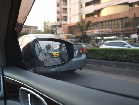 onboard: Car on-board driver looking outside to side mirror, inside mirror show a lot of car jam on street.