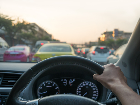 onboard: Car on-board view of hand holding steering wheel in car park on bad traffic street. Stock Photo
