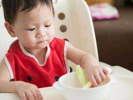 Asian toddler learn to eat meal herself. Фото со стока