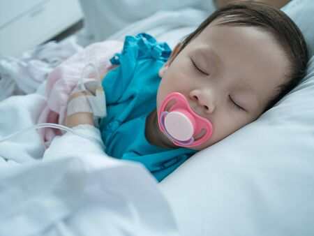 recieving: Baby sleeping in sickbed in hospital in recieving intravenous solution with pacifier in mouth.