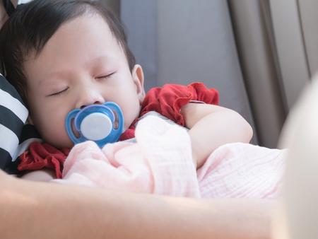 personas abrazadas: Sueño del bebé en coche con el chupete en la boca. sueño Niño asiático en la mano madre.