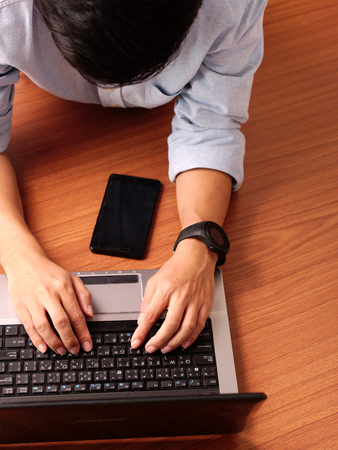 Closeup of a man laying typing on laptop wearing smart-watch and mobilephone beside.