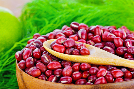 Red azuki beans in wooden bowl on white background. Stock Photo