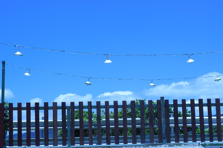 deteriorated: Wooden fence with sky and power lines with a lamp in the background