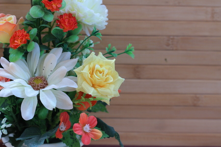 antecedents: Beautiful flowers in a vase on a wooden brown background