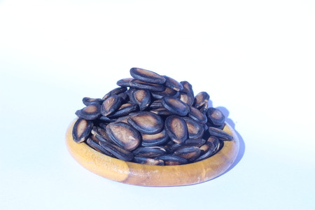 edibles: Watermelon seeds piled in brown wooden plate on a white background