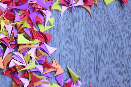 colored paper: Beautiful colored paper cut into small pieces and piled on the old wooden gray background