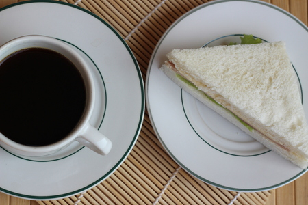blake and white: Black coffee and sandwich lay on a brown background