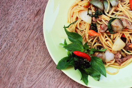 carnes y verduras: Stir spa-style spaghetti with Thai style meat in a green dish on a brown background