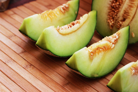 Melon fruit is spherical, has a rough texture and delicious sweet taste is cut on  brown background. Stock Photo