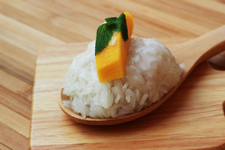 Mango sticky rice is put in a wooden container placed on a brown wooden table