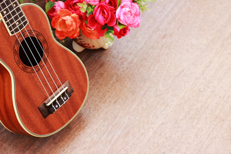 Brown Ukulele Lay on Old Brown Wood Table Stock Photo