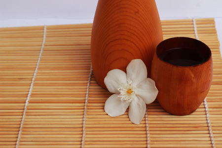 SAKE liqueur in a brown wooden bottle on a light brown background. Stock Photo