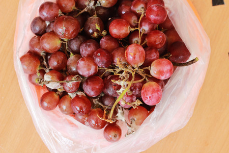 The rotten grapes are molded in a plastic bag on a brown table. Stock Photo