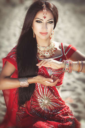Beautiful young indian woman in traditional clothing with bridal makeup and jewelry  photo