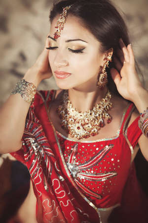 Beautiful young indian woman in traditional clothing with bridal makeup and jewelry