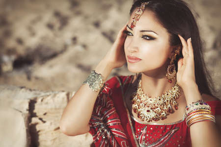 Beautiful young indian woman in traditional clothing with bridal makeup and jewelry  gorgeous brunette bride traditionally dressed Outdoors in India  Girl bollywood dancer in Sari  Arabian bellydancer