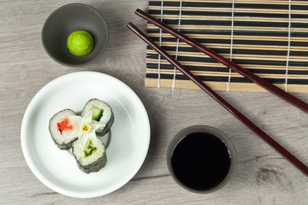 susi: fresh sushi roll with wasabi and soya sauce on the susi roll mat and grey table. Stock Photo