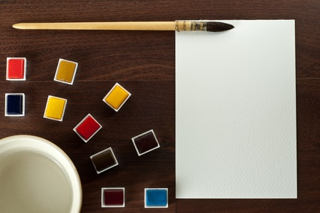 tabel: Vintage watercolor paint with  brush and blank paper on brown tabel. Top view. Stock Photo
